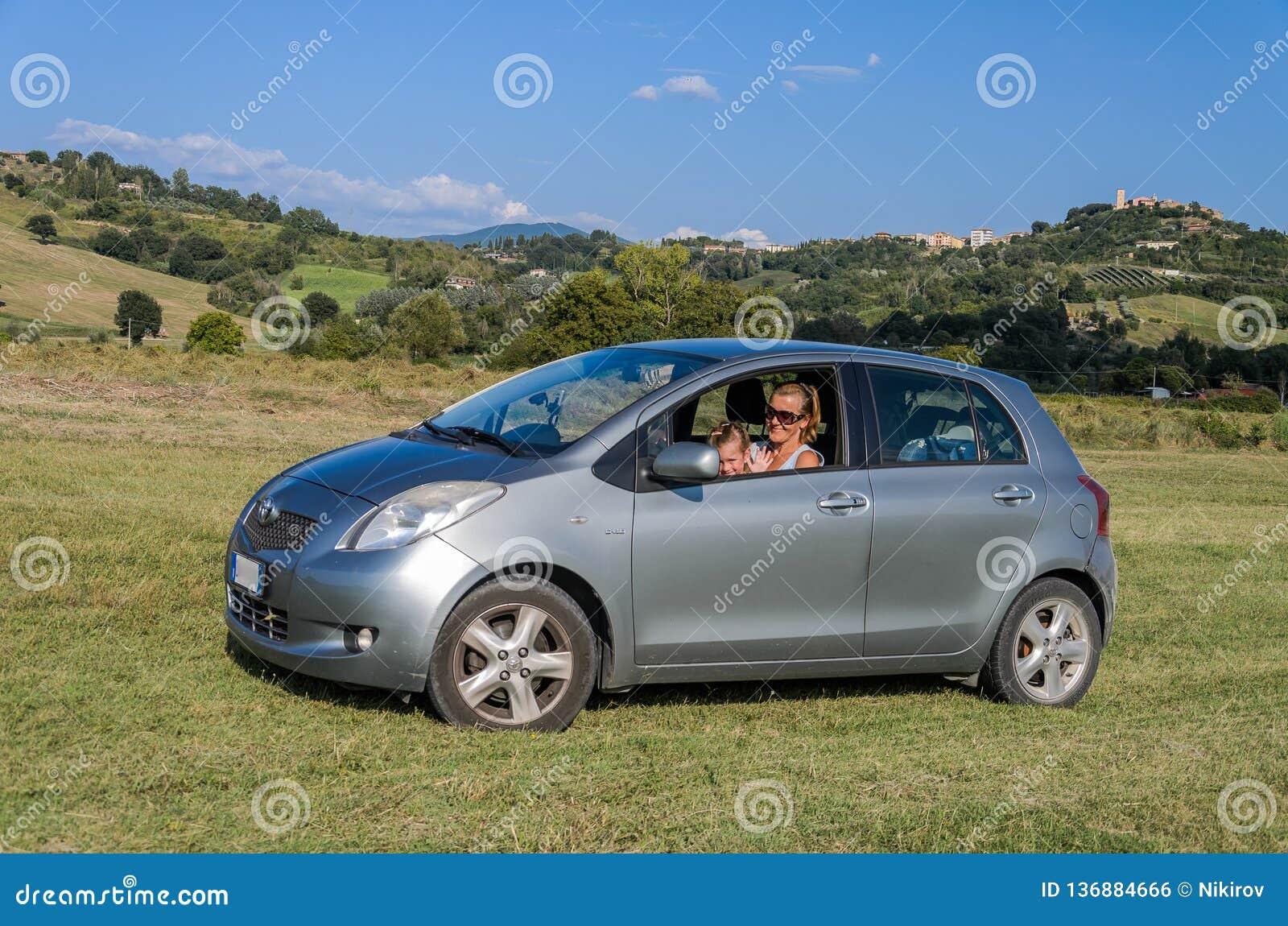 ROMA, ITALIA - AGOSTO DE 2018: Poco bebé adorable que conduce un coche de plata Toyota Yaris y su mamá están conduciendo a través