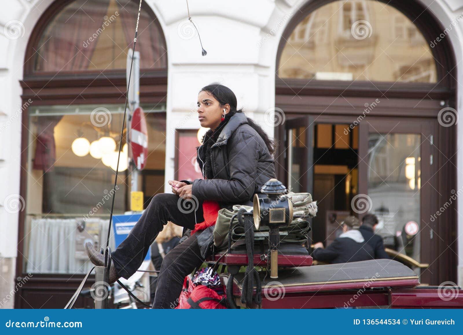 Roma, Italia, el 15 de octubre de 2011: La muchacha asiática hermosa controla un carro traído por caballo