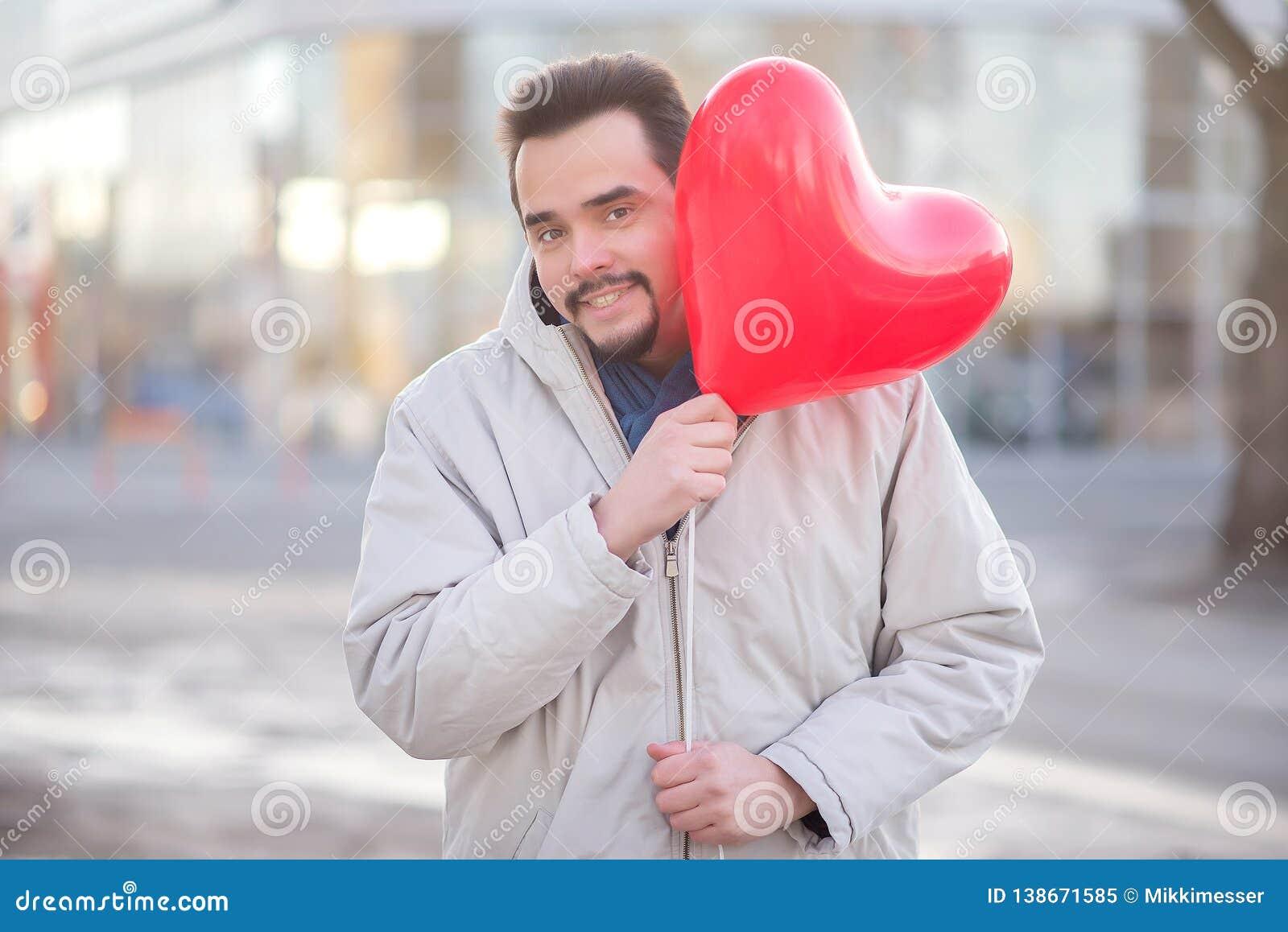 Roman urbain : jeune homme avec une barbe de hippie attendant une date et regardant en plaisantant du ballon à air en forme de co
