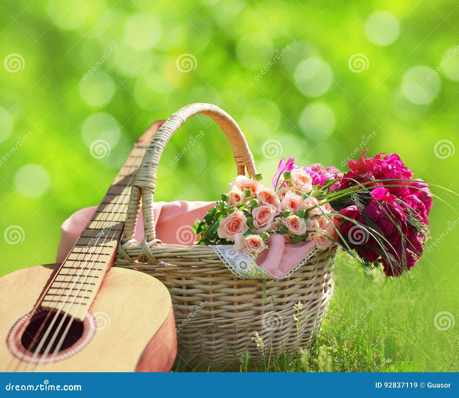 Romance, amor, concepto del día del ` s de la tarjeta del día de San Valentín - cesta de mimbre con el ramo de flores, guitarra e