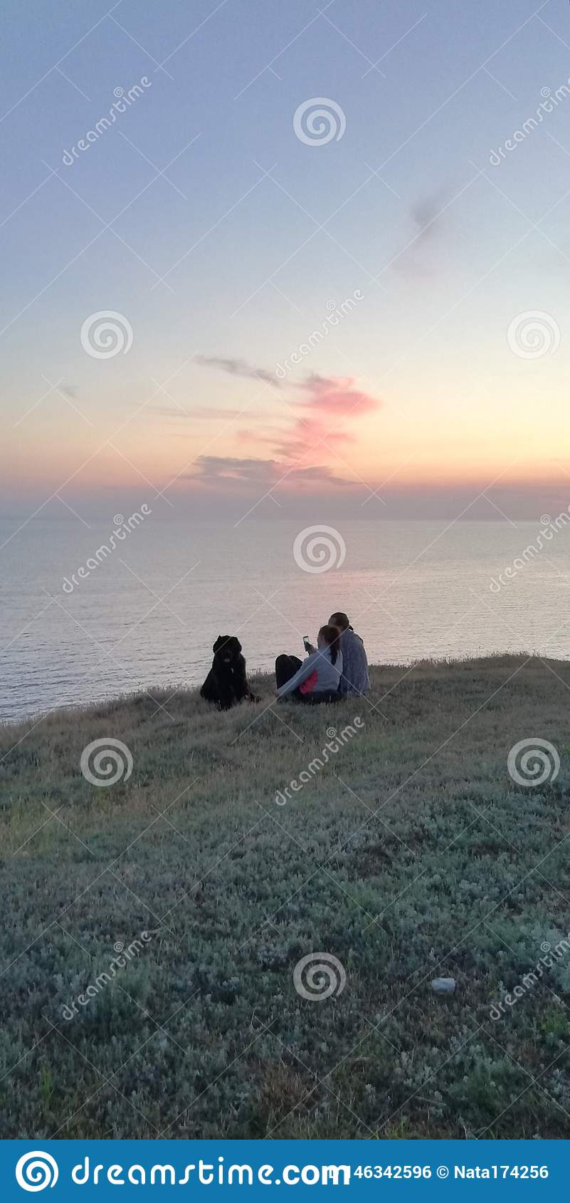 Summer evening. Family with a dog by the sea