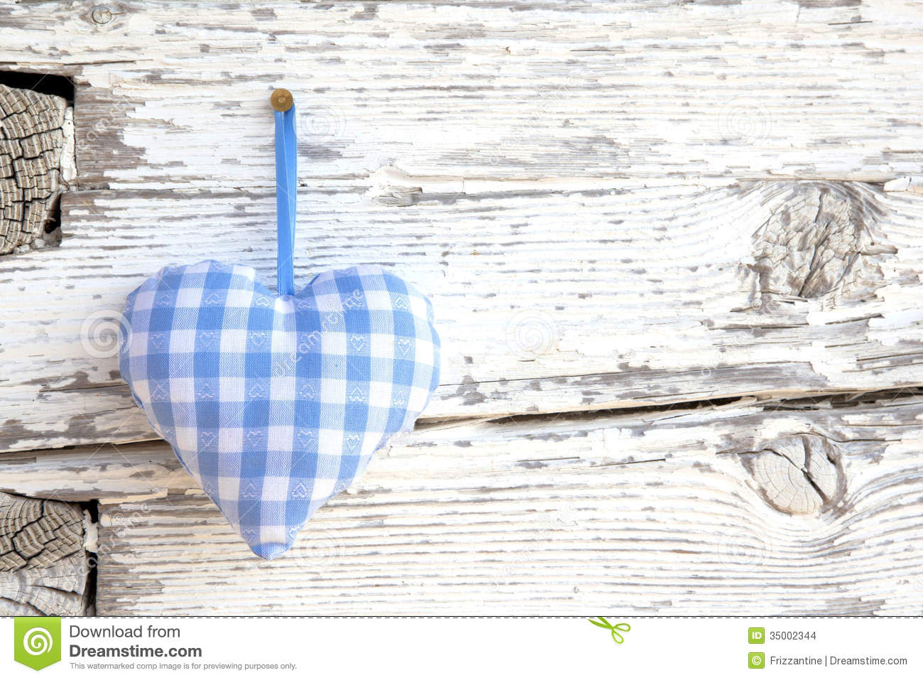 Romantic blue/white checkered heart shape hanging above white wooden surface on a nail- white wooden shabby chic background for