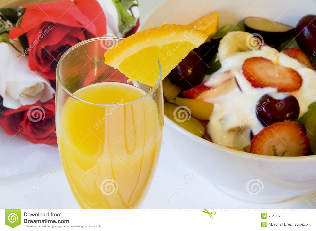 tray of fruit and juice placed on a heart themed bed with rose and ...
