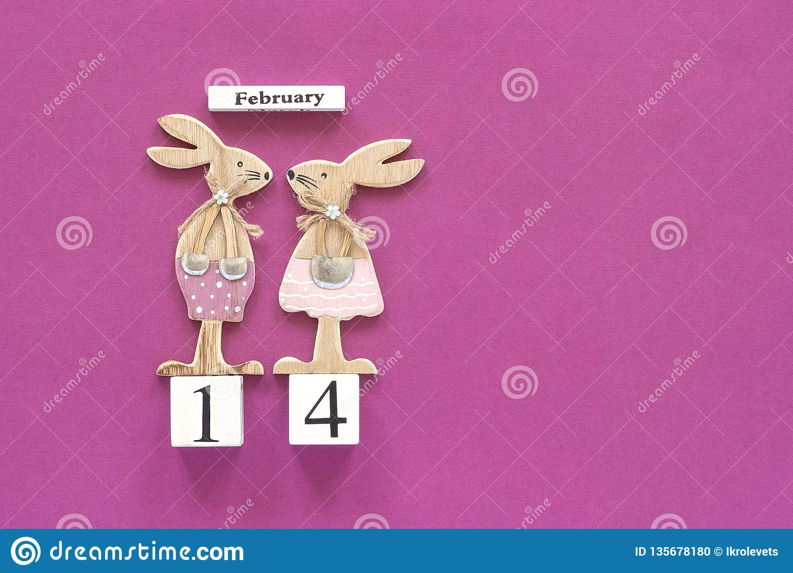 Romantic composition Wooden cubes calendar February 14th and pair of wooden lovers figurine rabbits on purple background. Concept