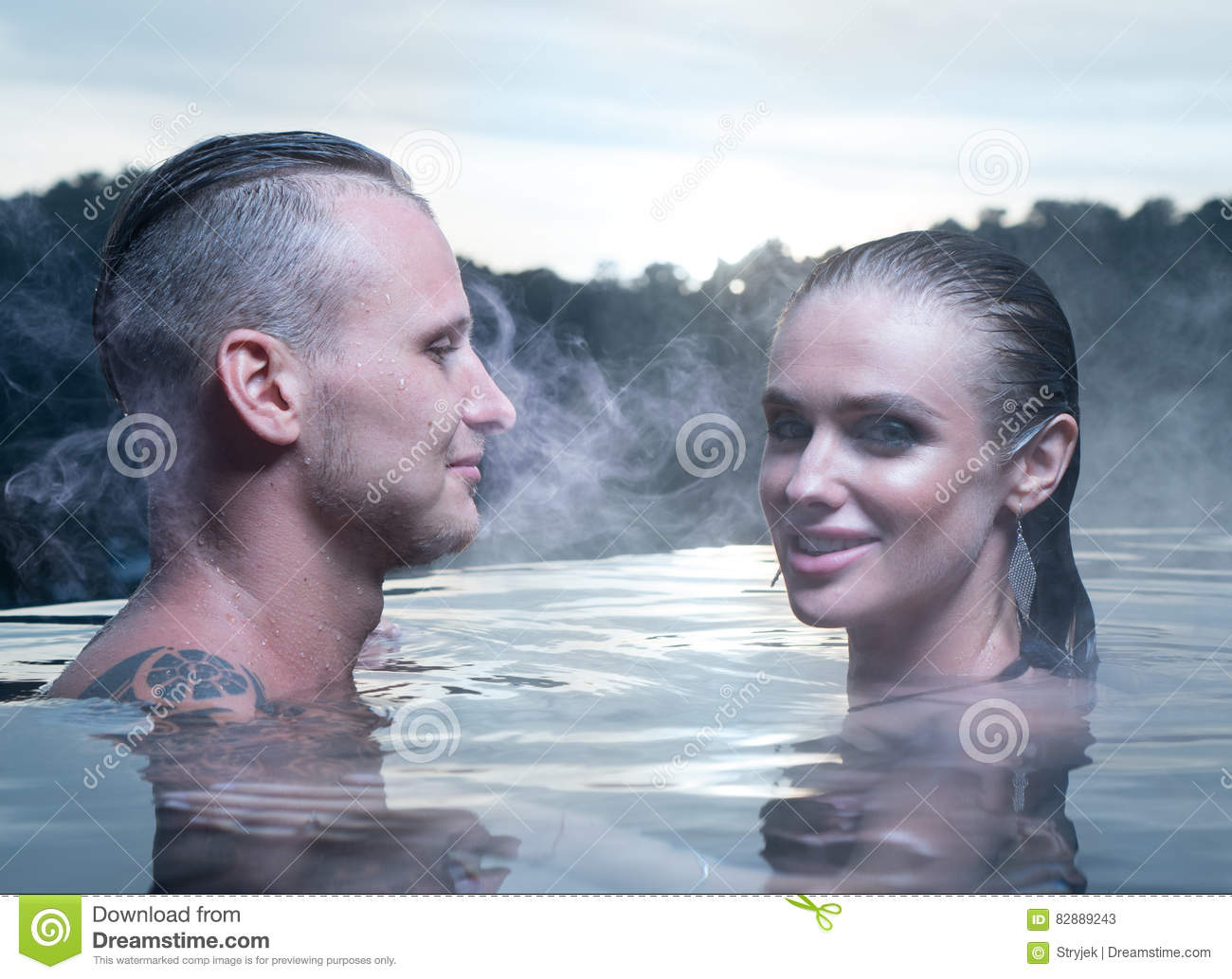 Romantic couple in love relaxing in hot pool on iceland young women and men enjoying bathing relaxed in blue water lagoon icelandic tourist attraction