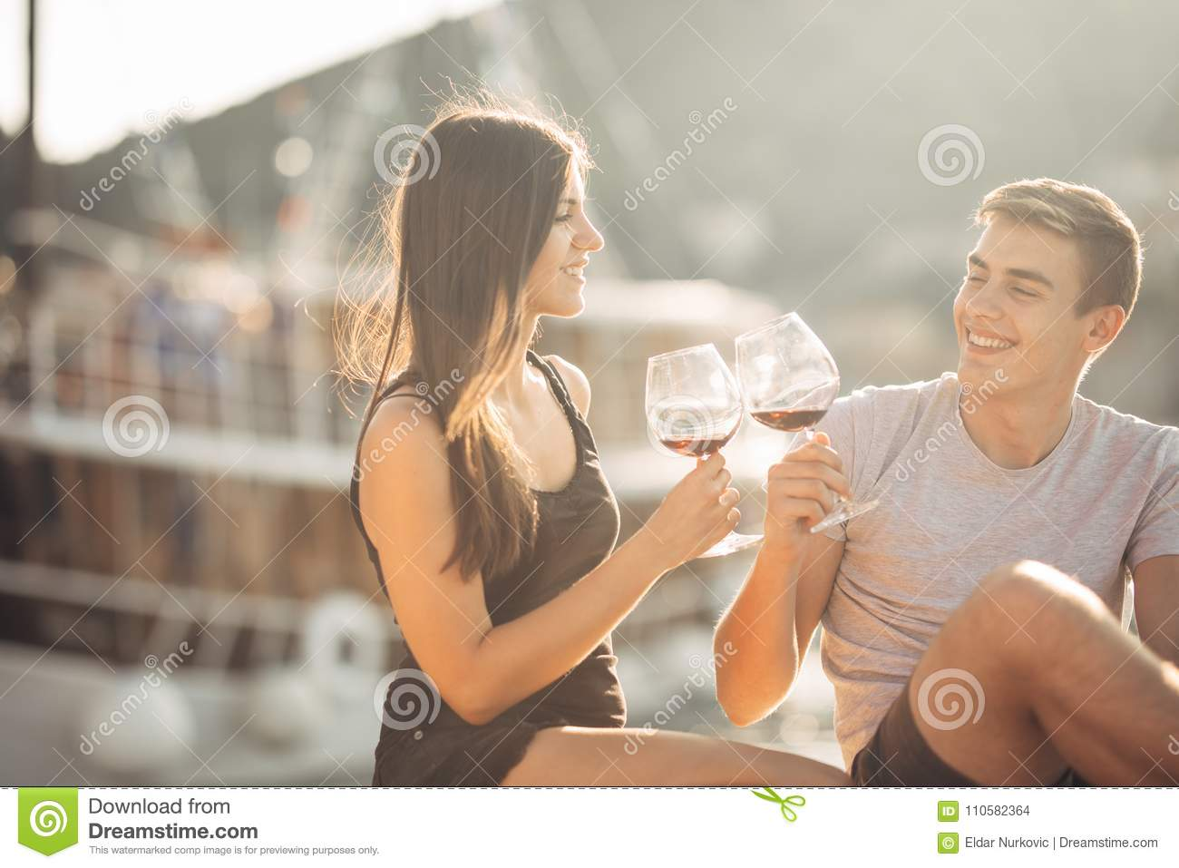 Romantic couple drinking wine at sunset.Romance.Two people having a romantic evening with a glass of wine near the sea.Cruise ship
