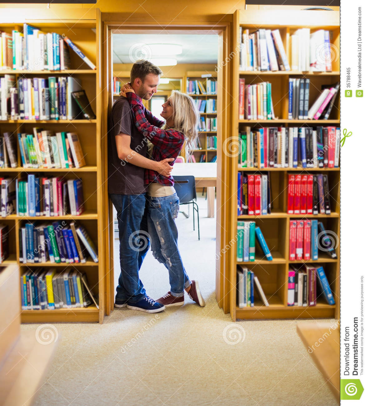 romantic couple embracing by bookshelves in library Bookshelf Home Office Ideas Bookshelves in Dining Room