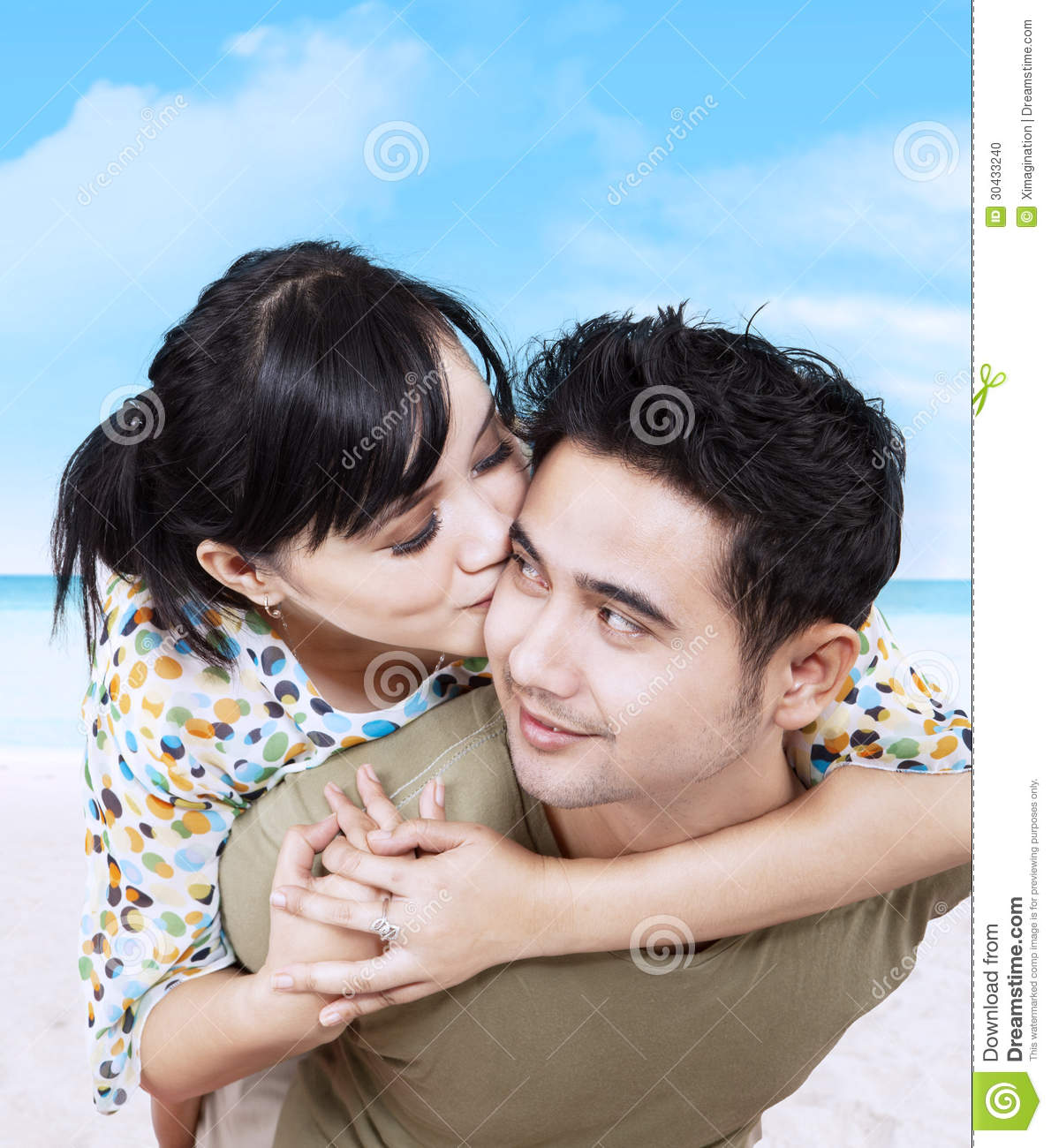 Happy Couple Sitting On Sandy Beach Embracing Kissing: Romantic Couple Hugging On The Beach Stock Photo