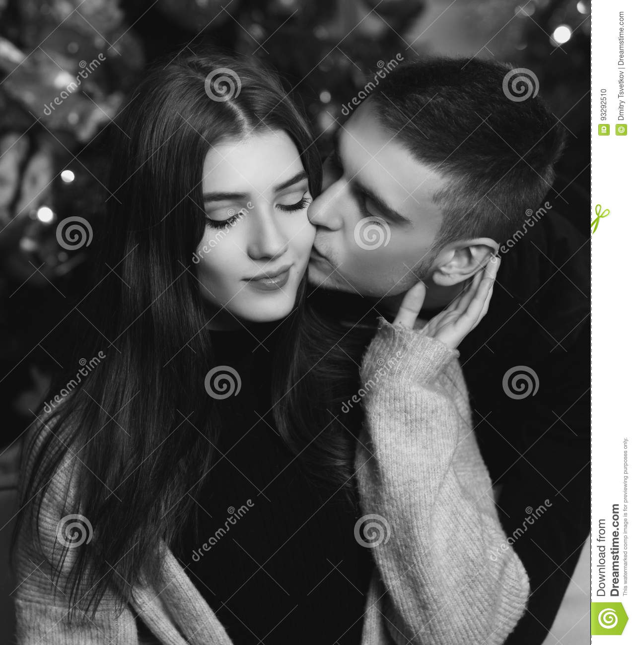 Young romantic cute couple staing at home and enjoying time together lovers hugging in cristmas decorated interior