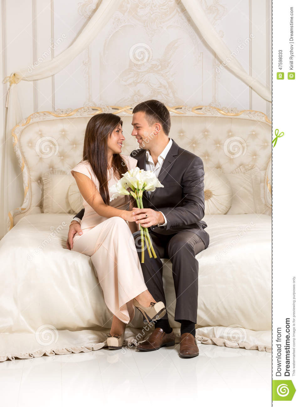 Romantic Couple In Love Sitting On Bed In Luxurious Room