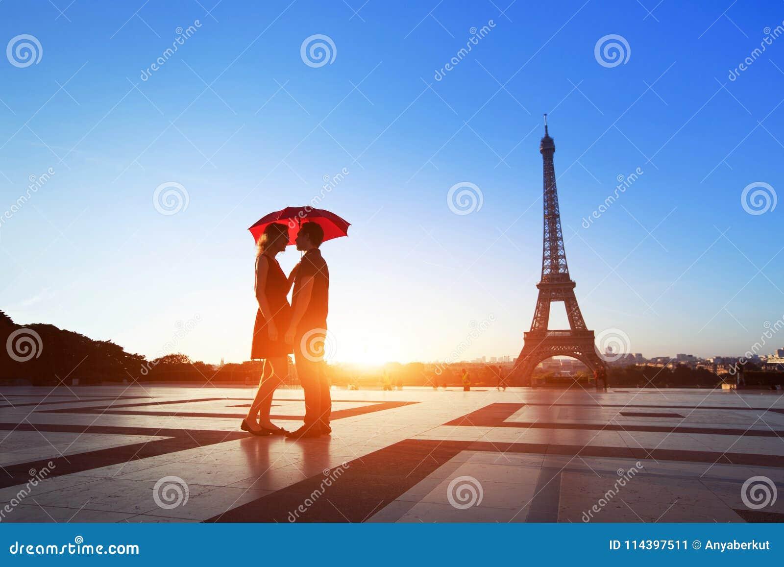 Romantic couple in Paris, man and woman under umbrella near Eiffel Tower