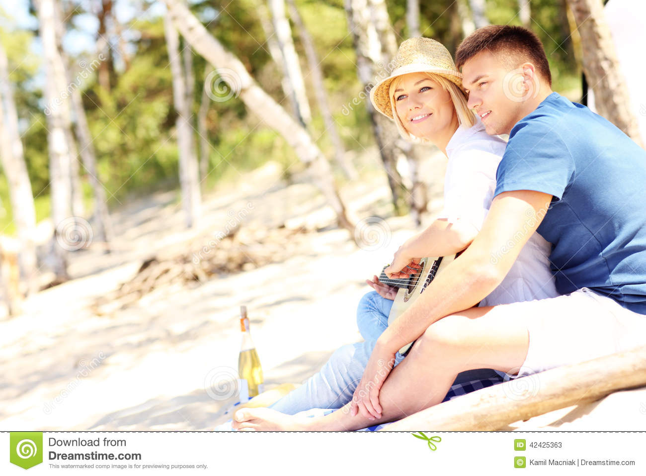 Romantic Couple Playing Guitar At The Beach Stock Photo