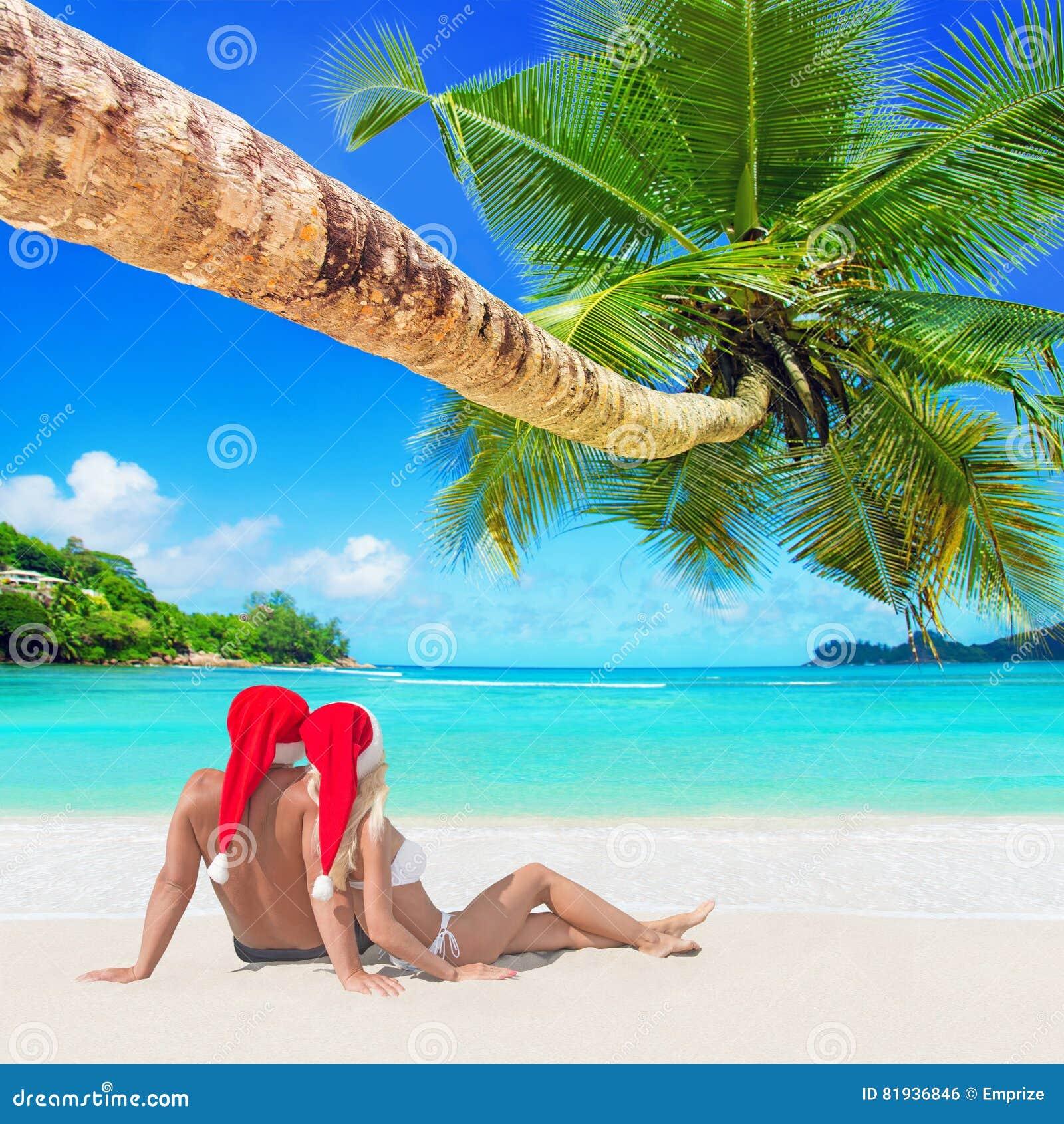 Romantic couple in red Christmas Santa hats sunbathe at tropical palm sandy island beach
