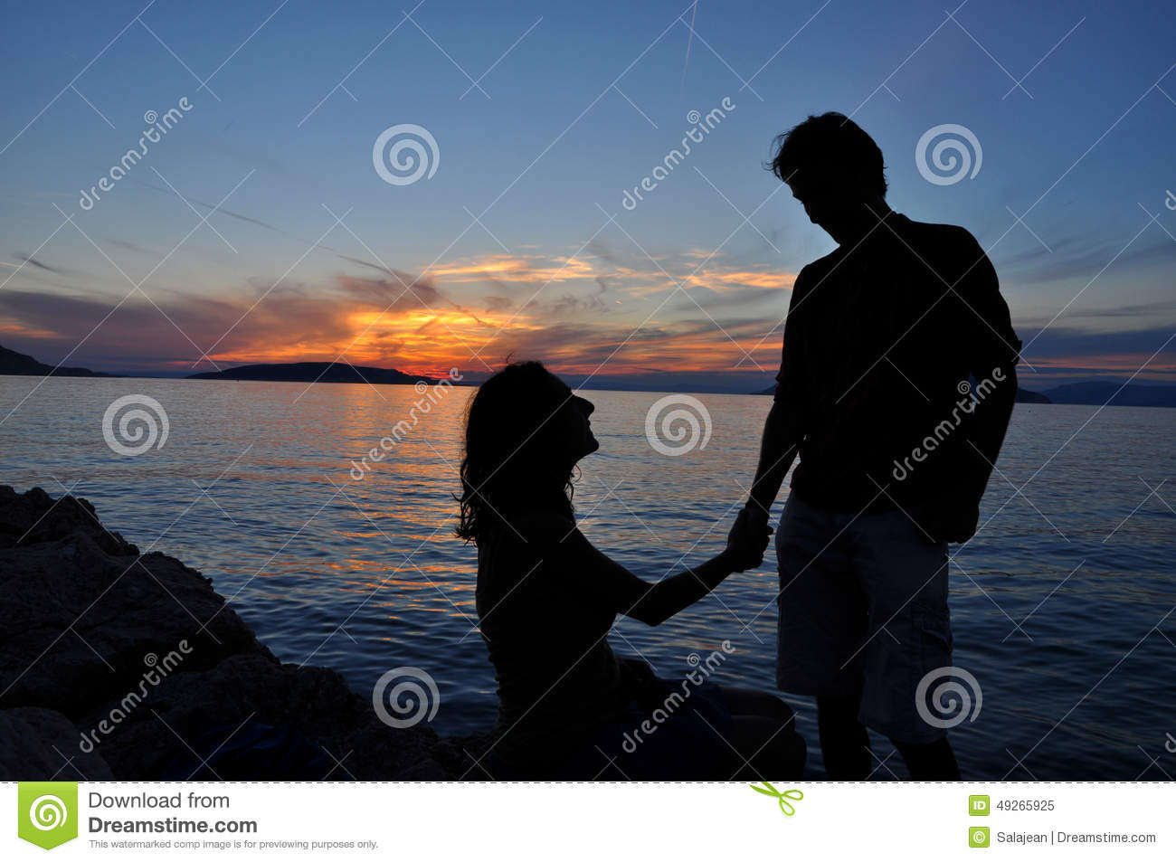 Romantic couple silhouette over sea sunset background