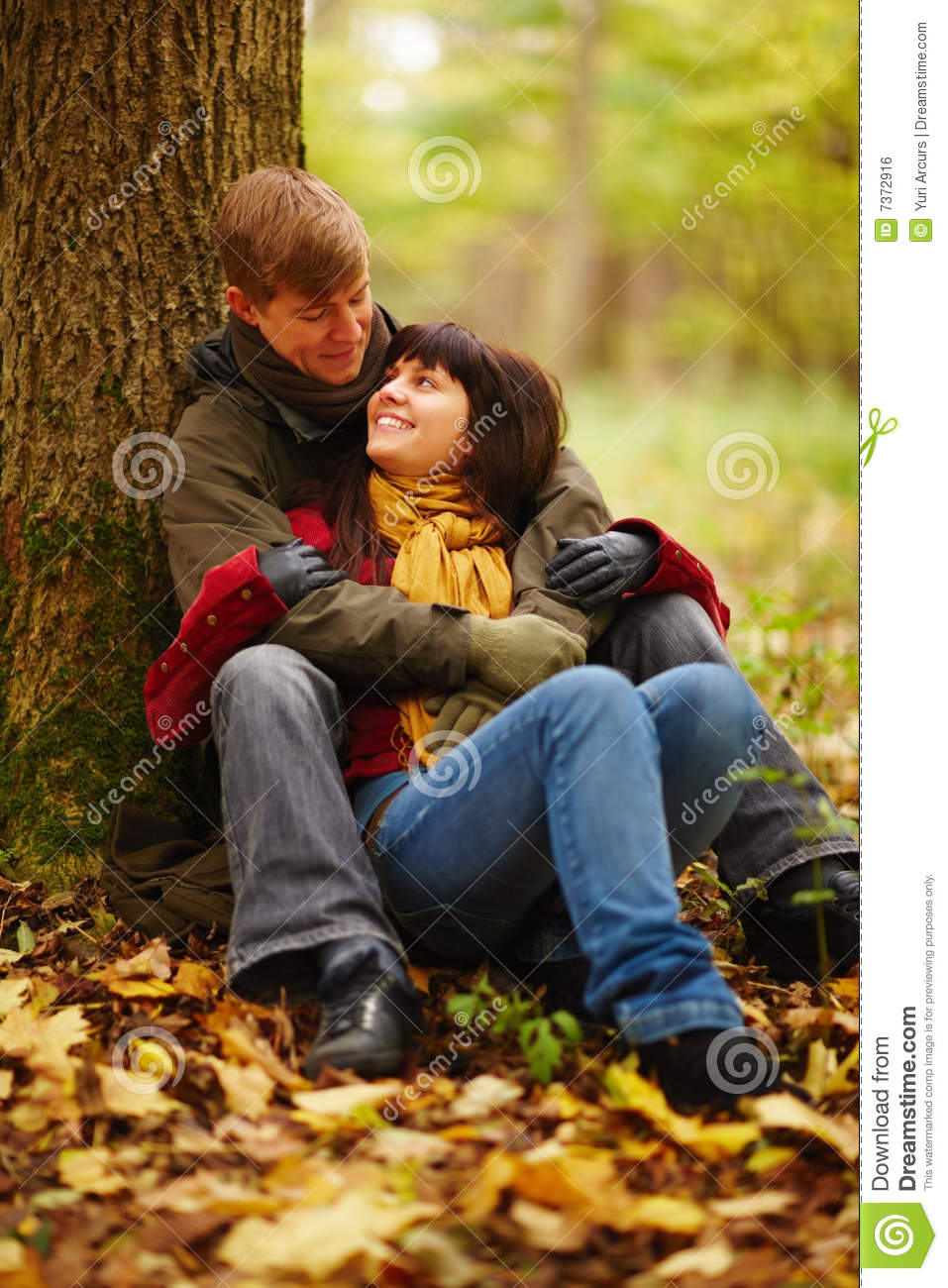 Romantic Couple Sitting Under A Tree Together Stock Photo