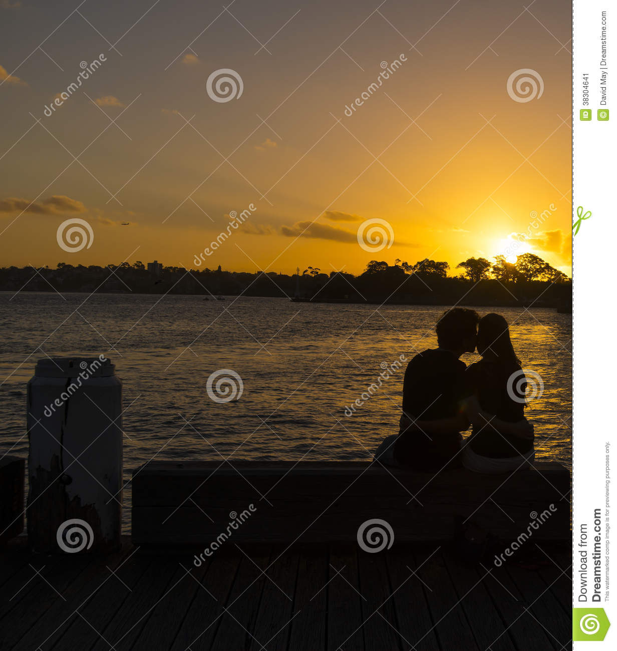Happy Couple Sitting On Sandy Beach Embracing Kissing: Romantic Couple Sunset Stock Image
