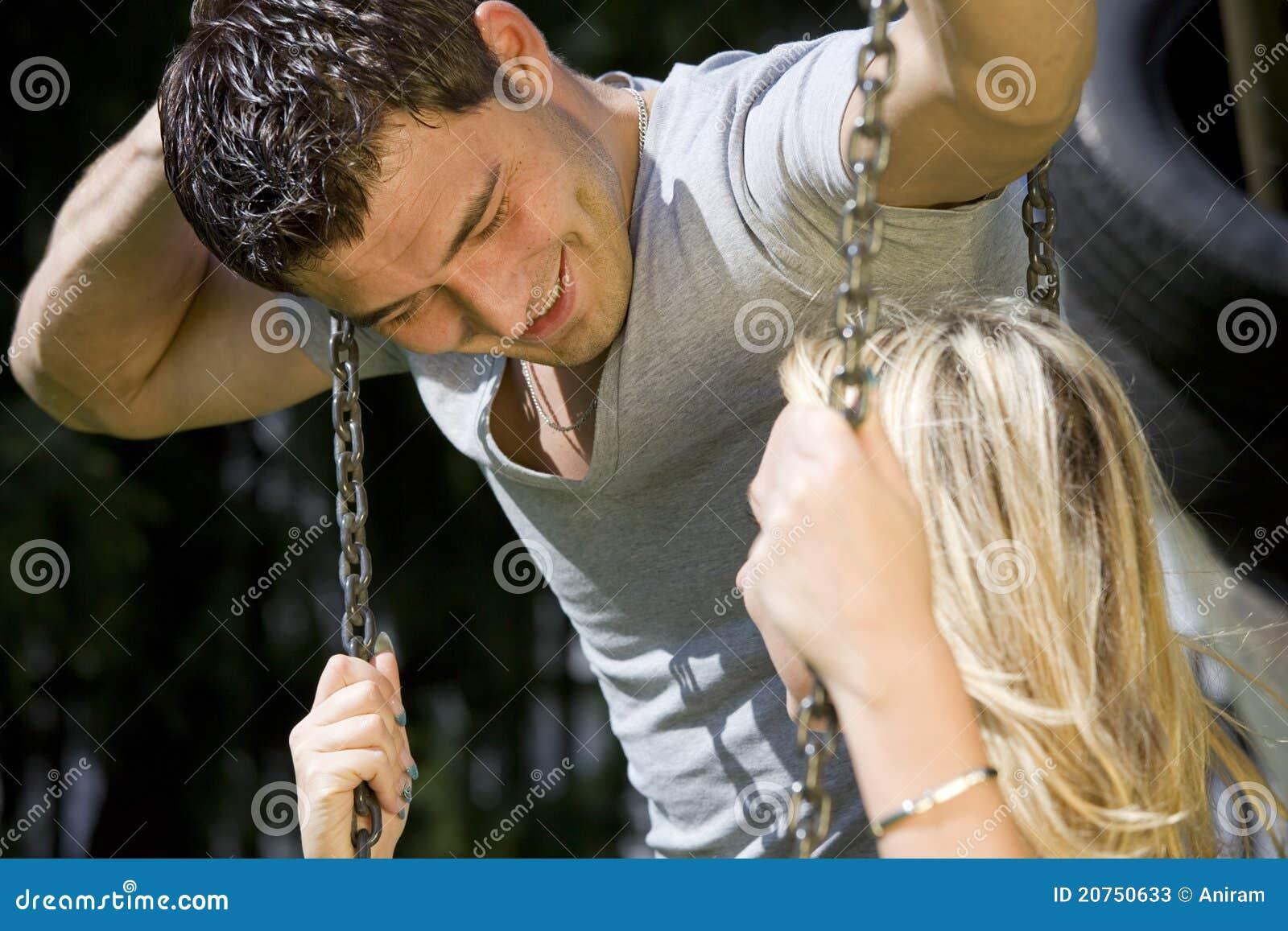 Romantic couple talking on a swing