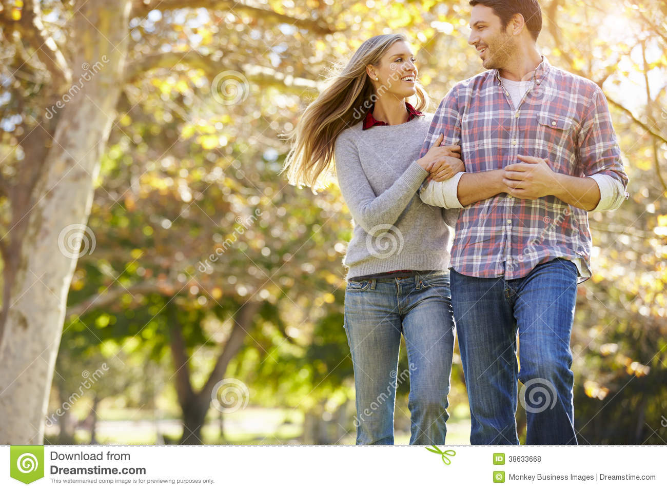 Romantic Couple Walking Through Autumn Woodland Royalty