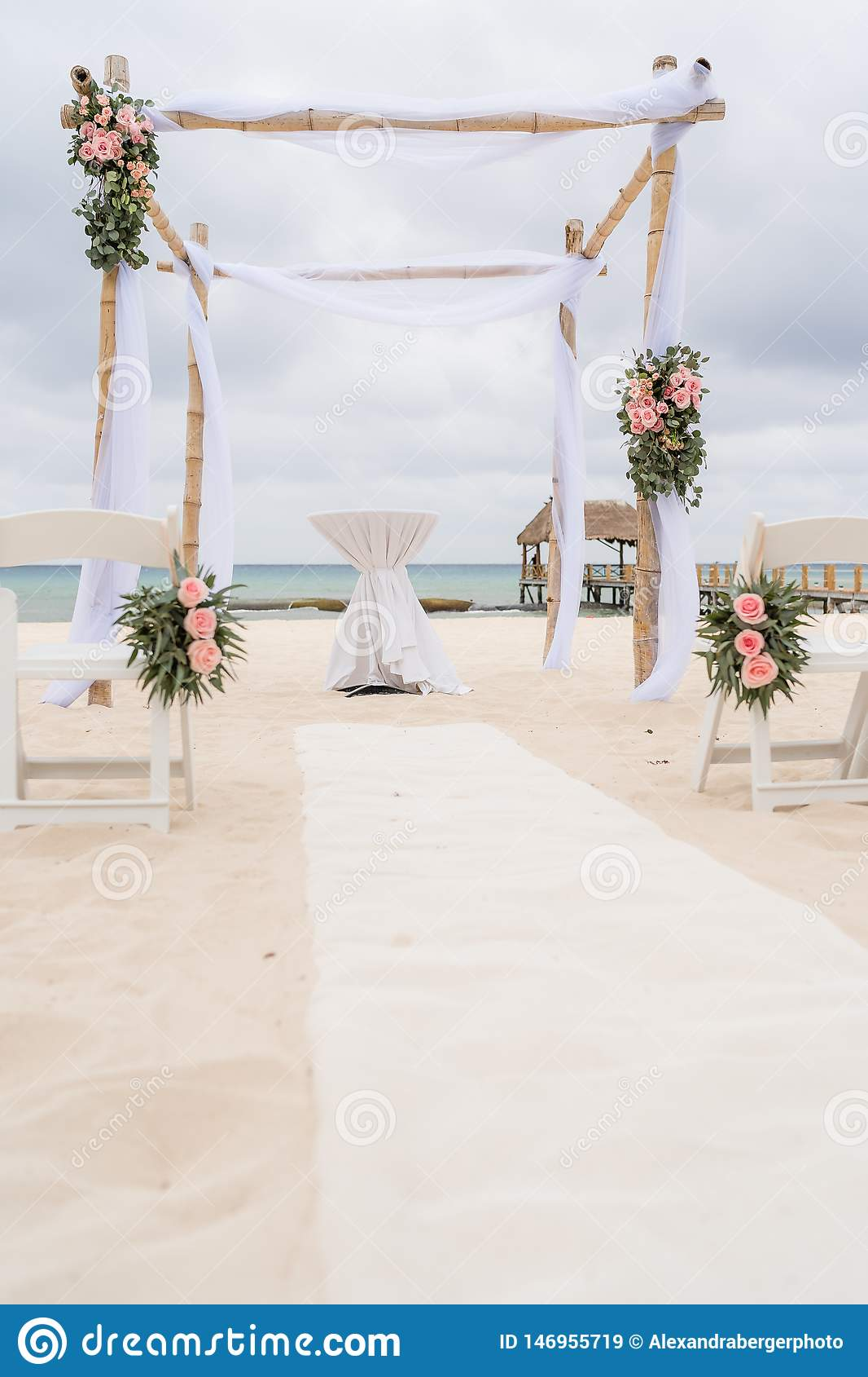 Romantic decoration of a pavilion of a beach wedding on the beach with sea in the background and cloudy sky