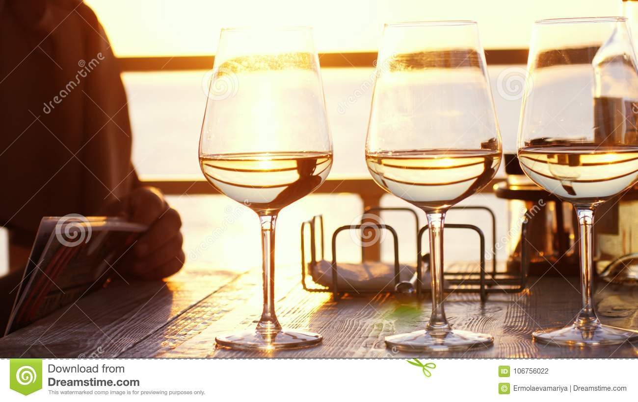 A romantic dinner in summer on a beach at sunset with three glasses of white wine and a bottle of the wine by the sea