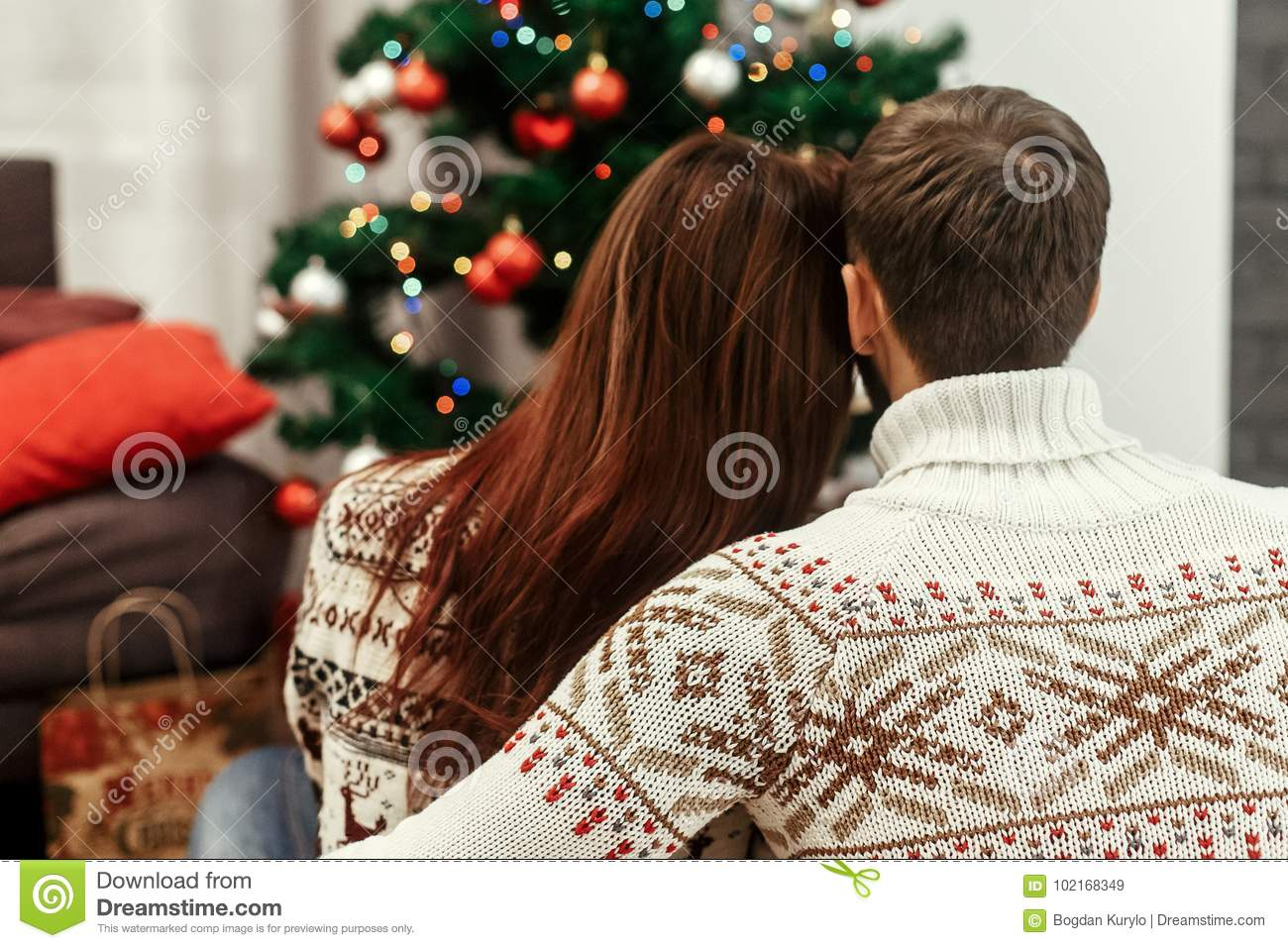 Romantic family couple in fashionable white sweaters hugging while looking at decorated christmas tree, greeting card concept wit