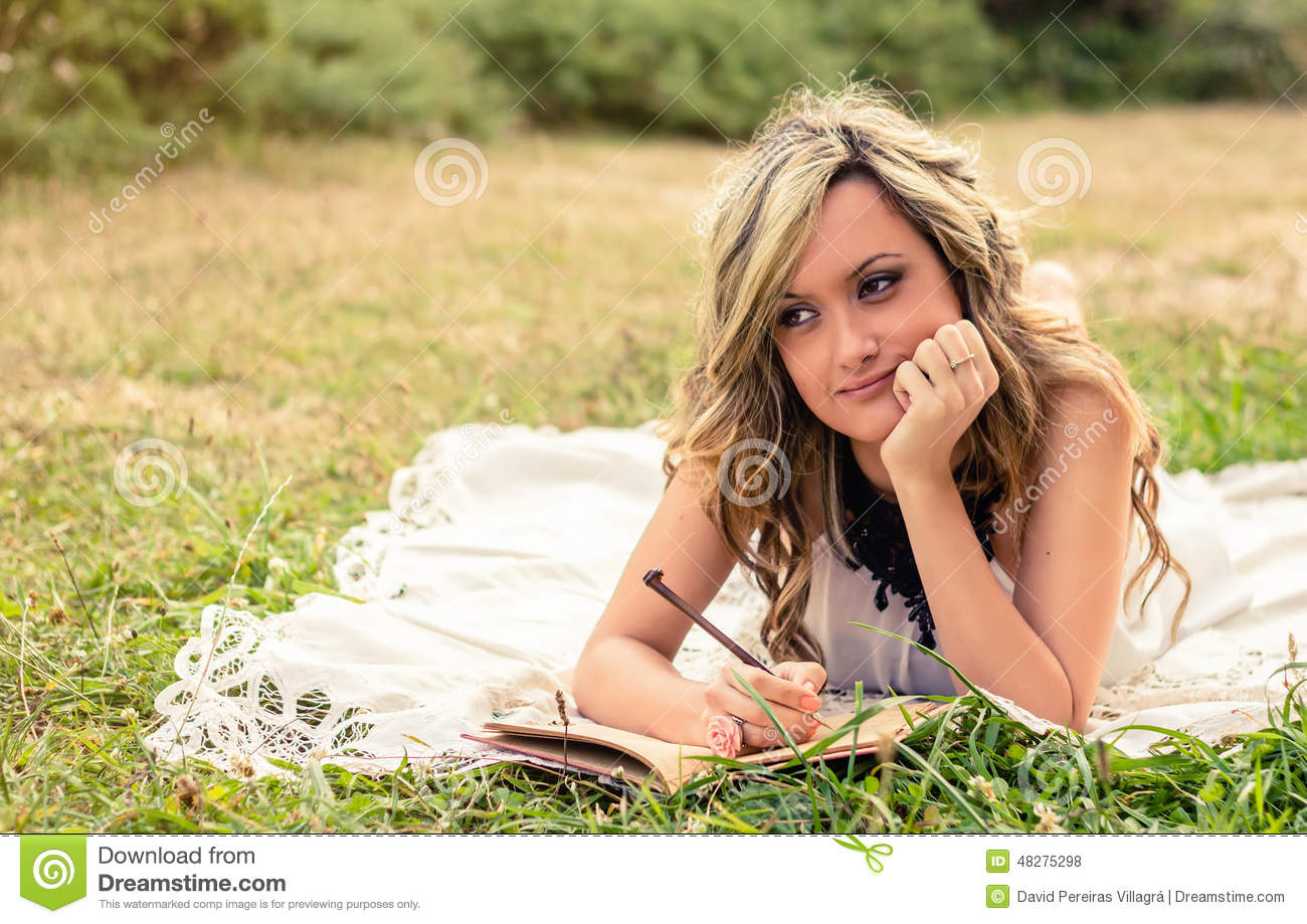 Romantic girl writing in a diary lying down stock photo image of romantic girl writing in a diary lying down publicscrutiny Gallery