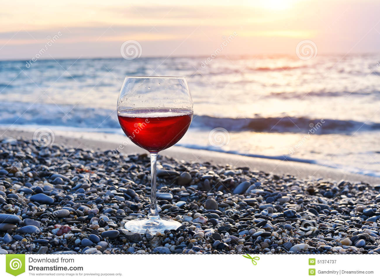 Romantic glass of wine sitting on the beach at colorful sunset, Glass of red wine against sunset, red wine on the sea ocean
