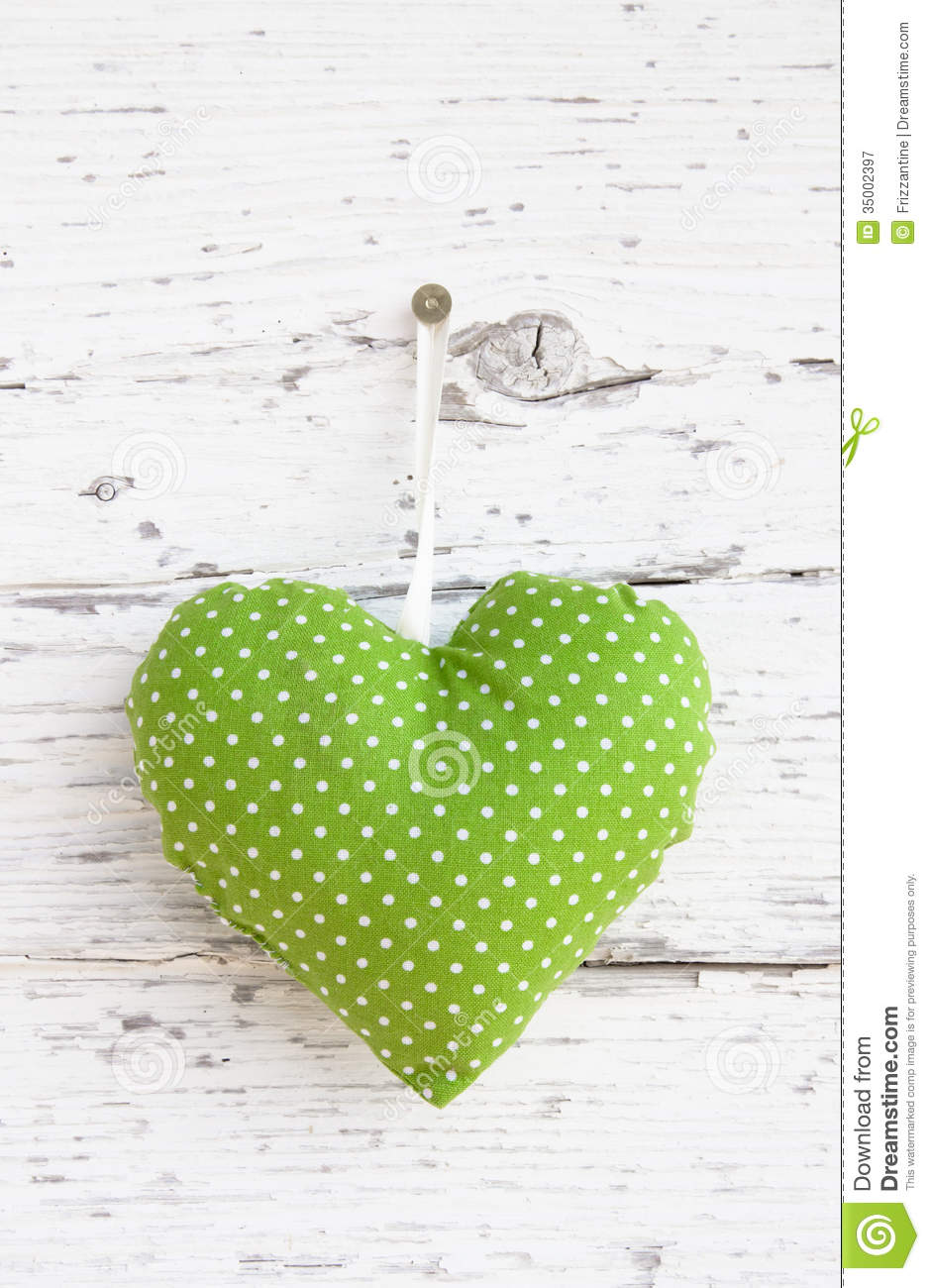 Romantic green dotted heart shape hanging above white wooden sur