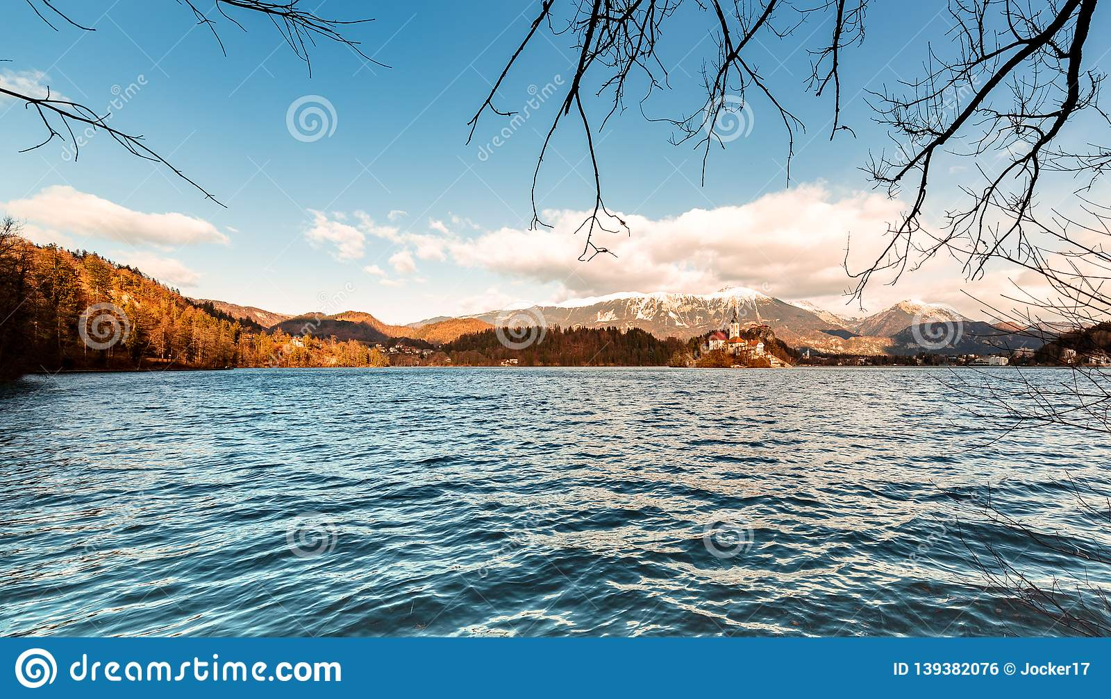 Romantic landscape at Lake Bled in Slovenia. Winter scenery sunny day, view of the church in the middle of the lake. Panorama