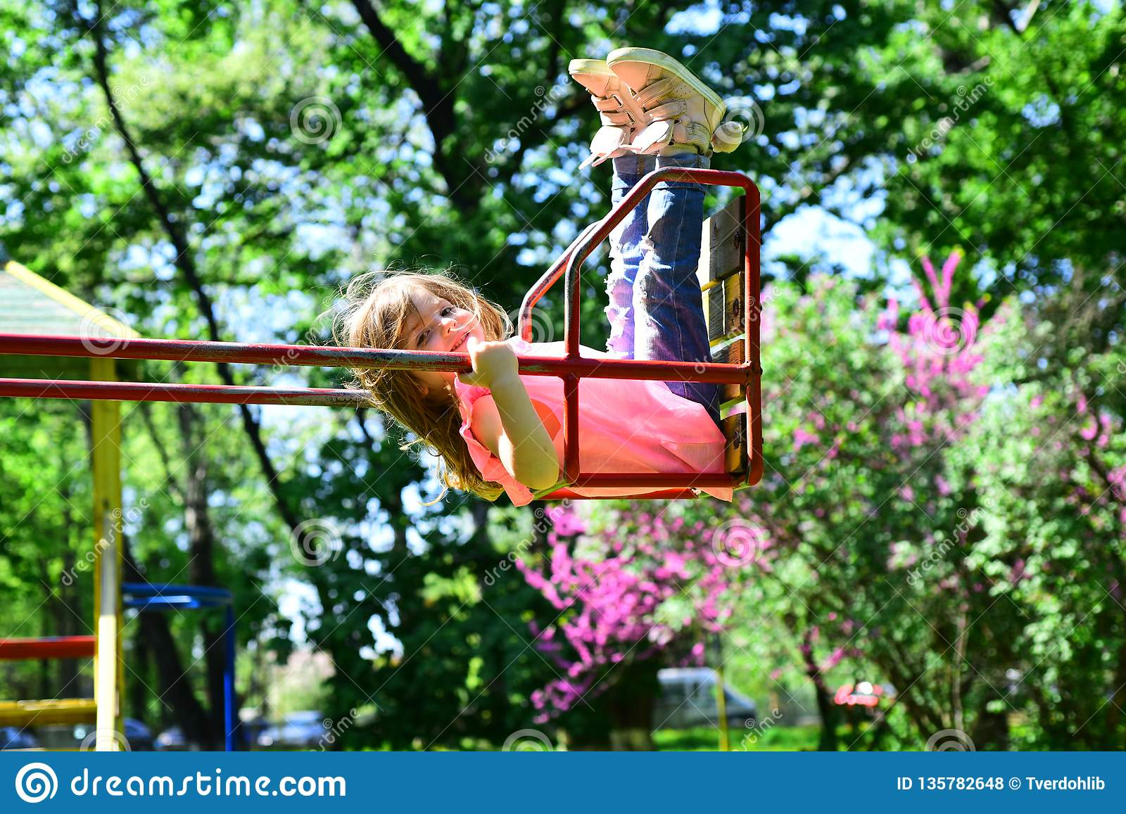 Romantic little girl on the swing, sweet dreams. Small kid playing in summer. childhood daydream .teen freedom