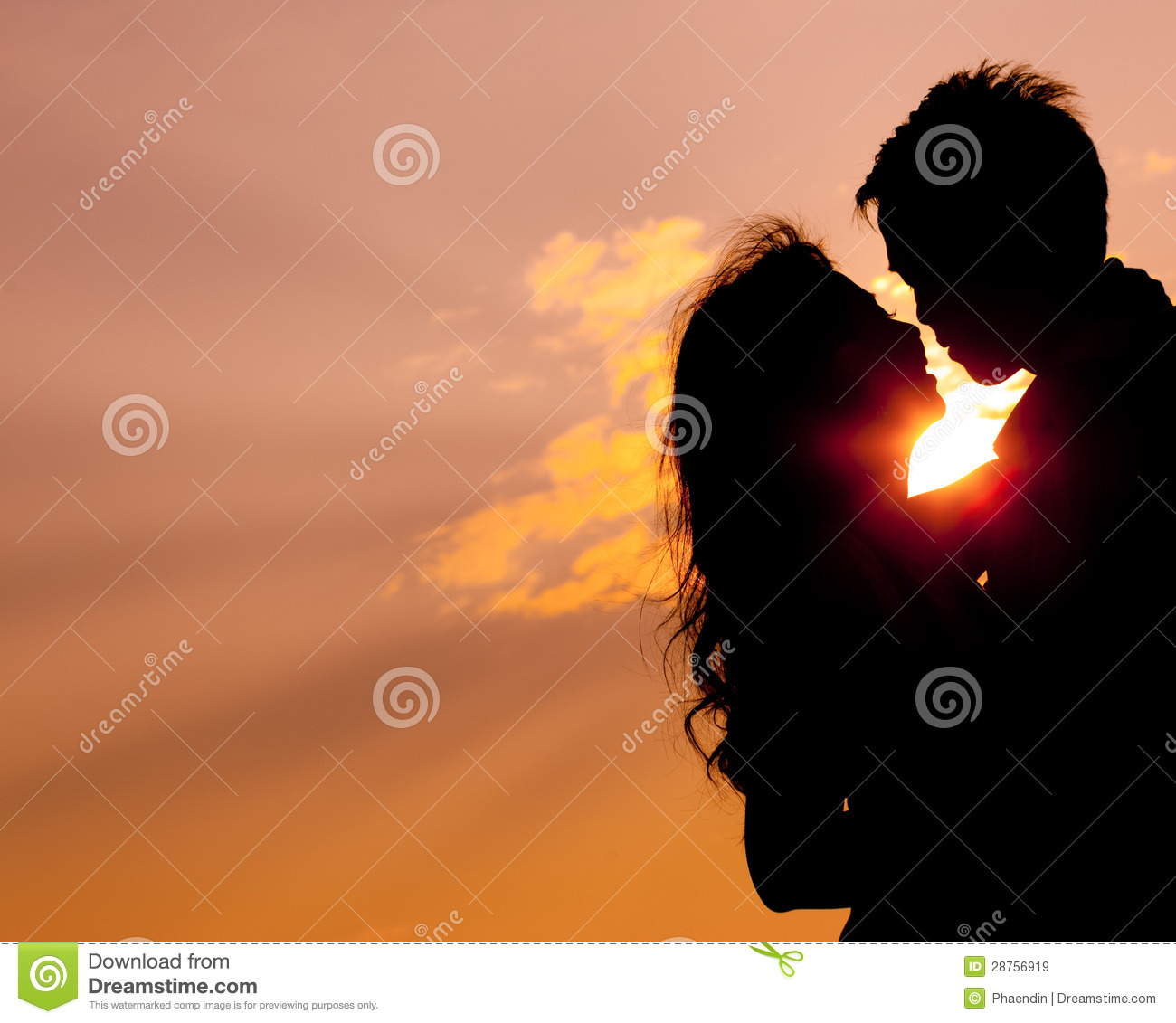Romantic lovers hugging at twlilight with sunset in background.