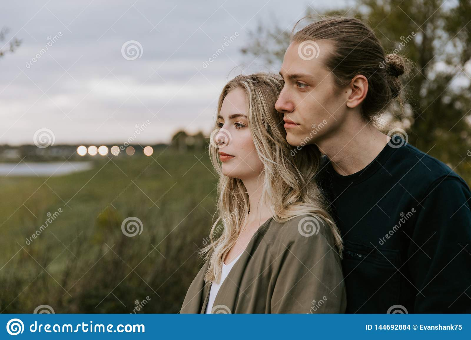 Romantic and Loving Young Adult Couple at the Park Looking At Nature and the Horizon for Portrait Pictures