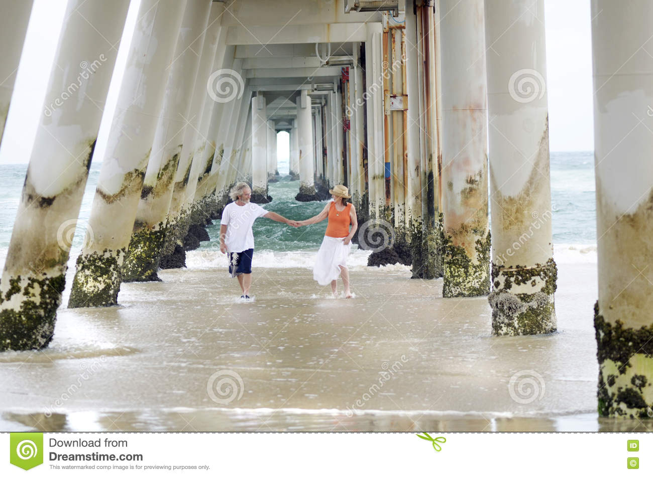Romantic older mature man & woman couple carefree on beach summer time
