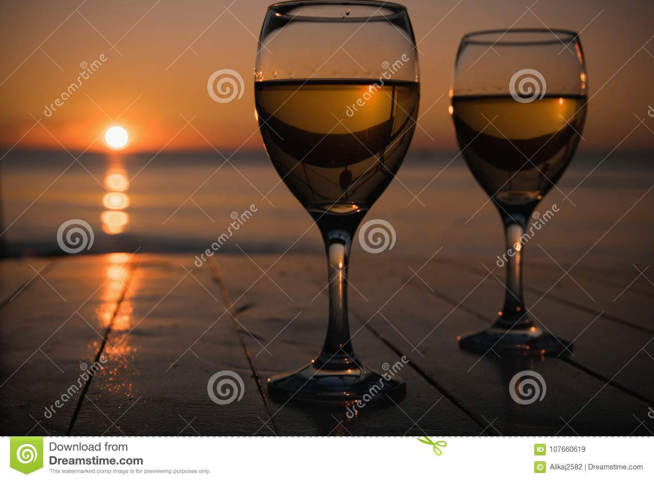 Romantic outdoor activity. Two glasses with white wine in an outdoor restaurant with sunset sea view, relaxation concept for two