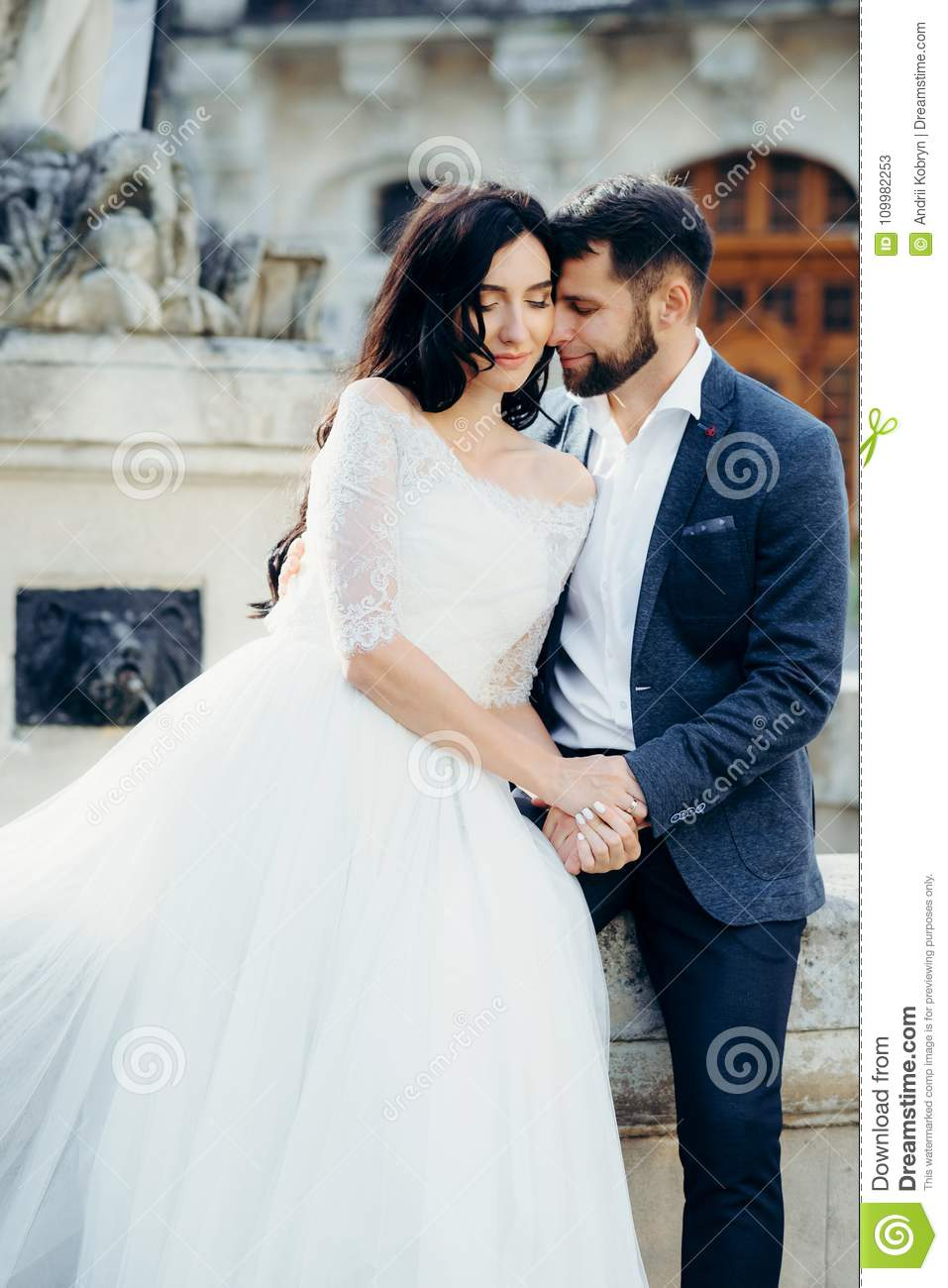 Romantic Outdoor Portrait Of The Beautiful Couple Of Newlyweds Tenderly Holding Hands And Touching Faces While Sitting Stock Image Image Of Adult Outdoors 109982253