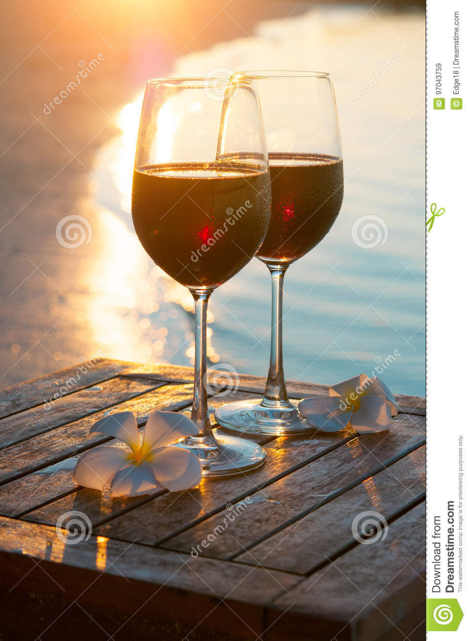 Romantic outdoor scene: two glasses of red wine at sea sunset