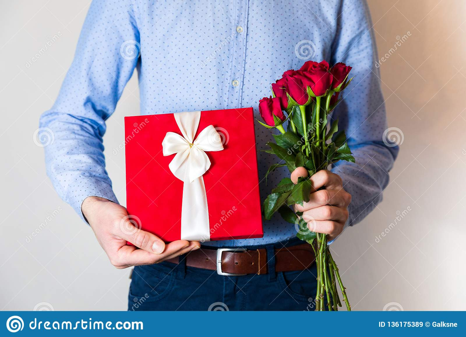 Valentines day surprise, love, handsome man holding romantic gift and red roses bouquet