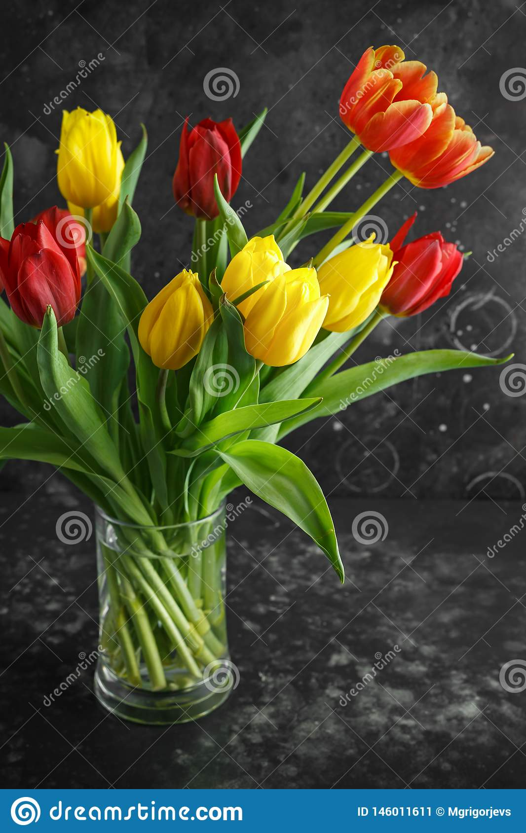 Romantic tulips bouqet on rustic dark background