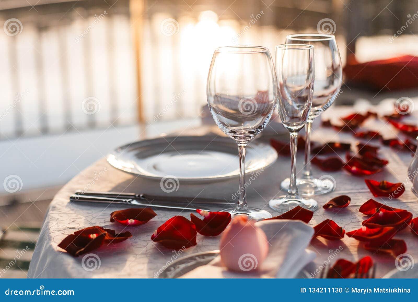 Romantic Valentine`s Day dinner setup with rose petals