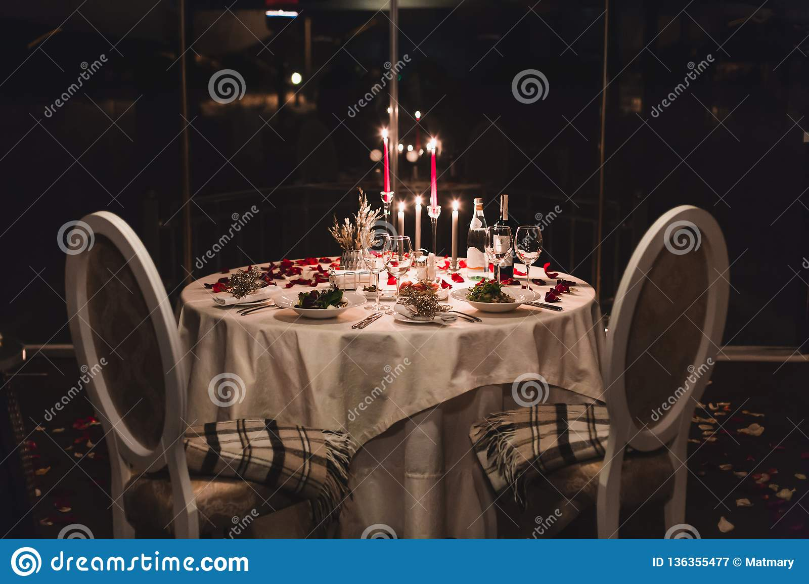 Romantic table setting with wine, beautiful flowers in box, empty glasses, rose petals and candles