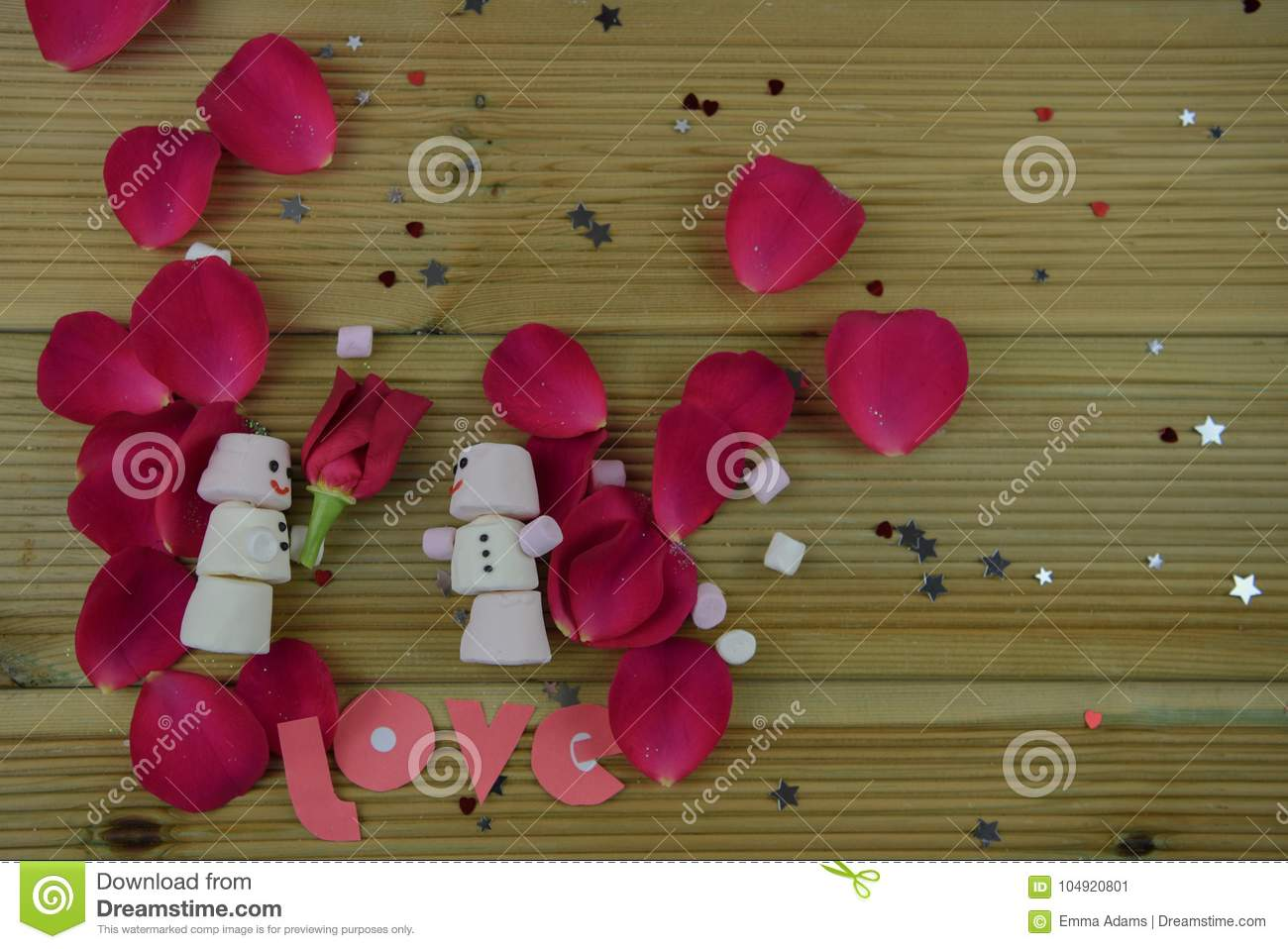 Romantic winter season photography image with marshmallows shaped as snowman with smiles iced on and holding a red rose flower