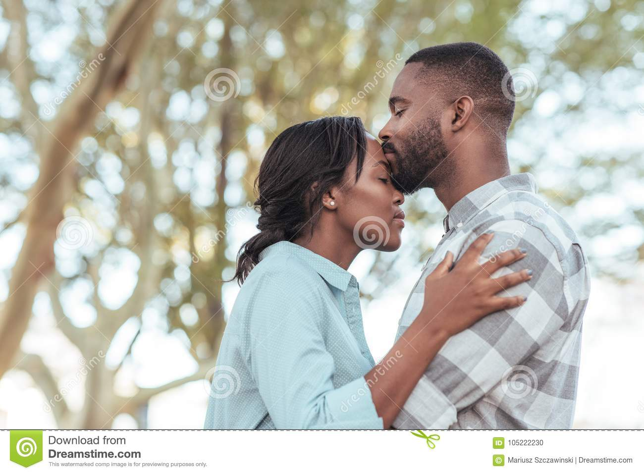 Romantic young African man kissing his girlfriend`s forehead outdoors