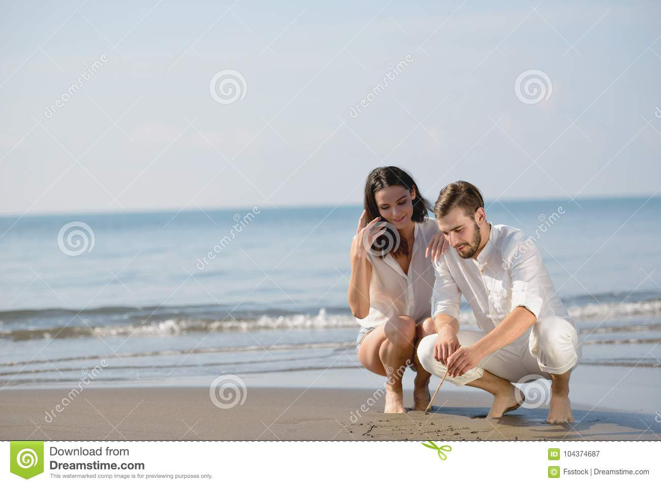 Romantic Young Couple Draw Heart Shapes In The Sand While On