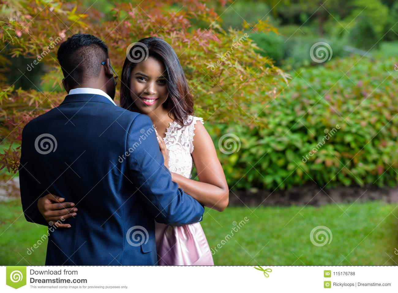 Romantic young couple hugging each other underneath colourful autumn trees