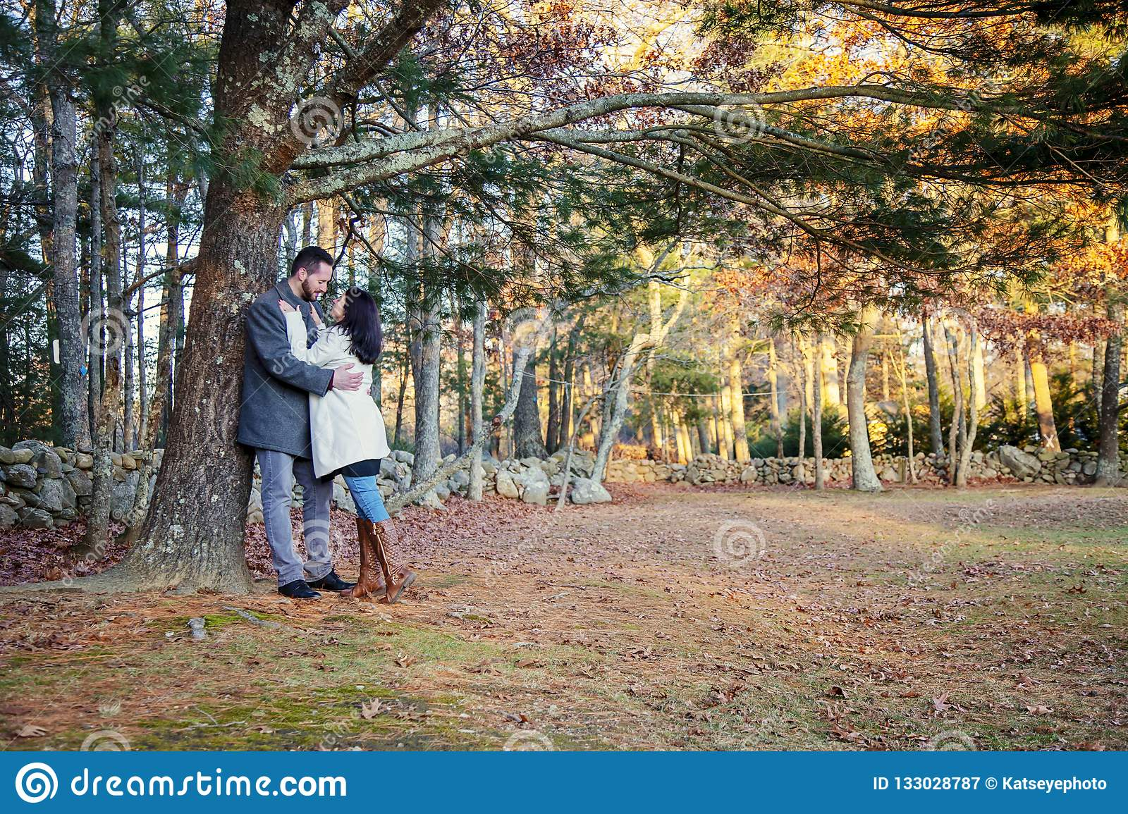 Romantic young couple hugging under a tree on a cold fall day