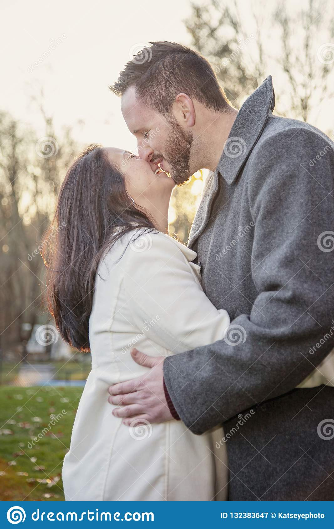Romantic young couple kissing and laughing outside on a cold fall day