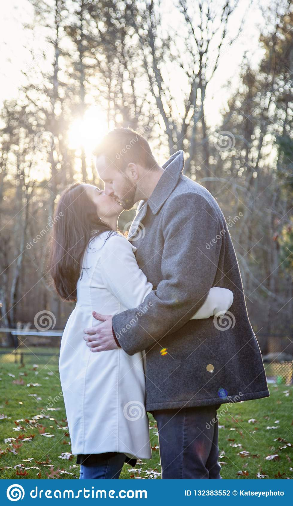 Romantic young couple kissing outside on a cold fall day
