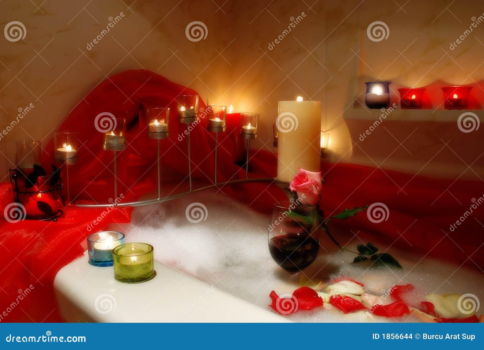 Badkuip die met kaarsen romantische atmosfeer wordt omringd