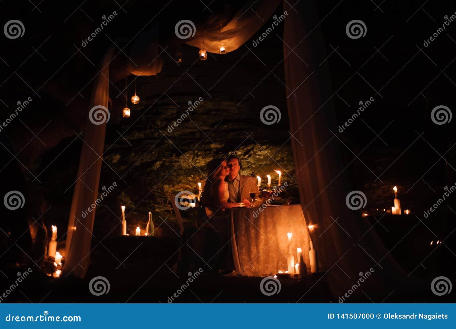 Romantisch diner van een jong paar door kaarslicht in de bergen