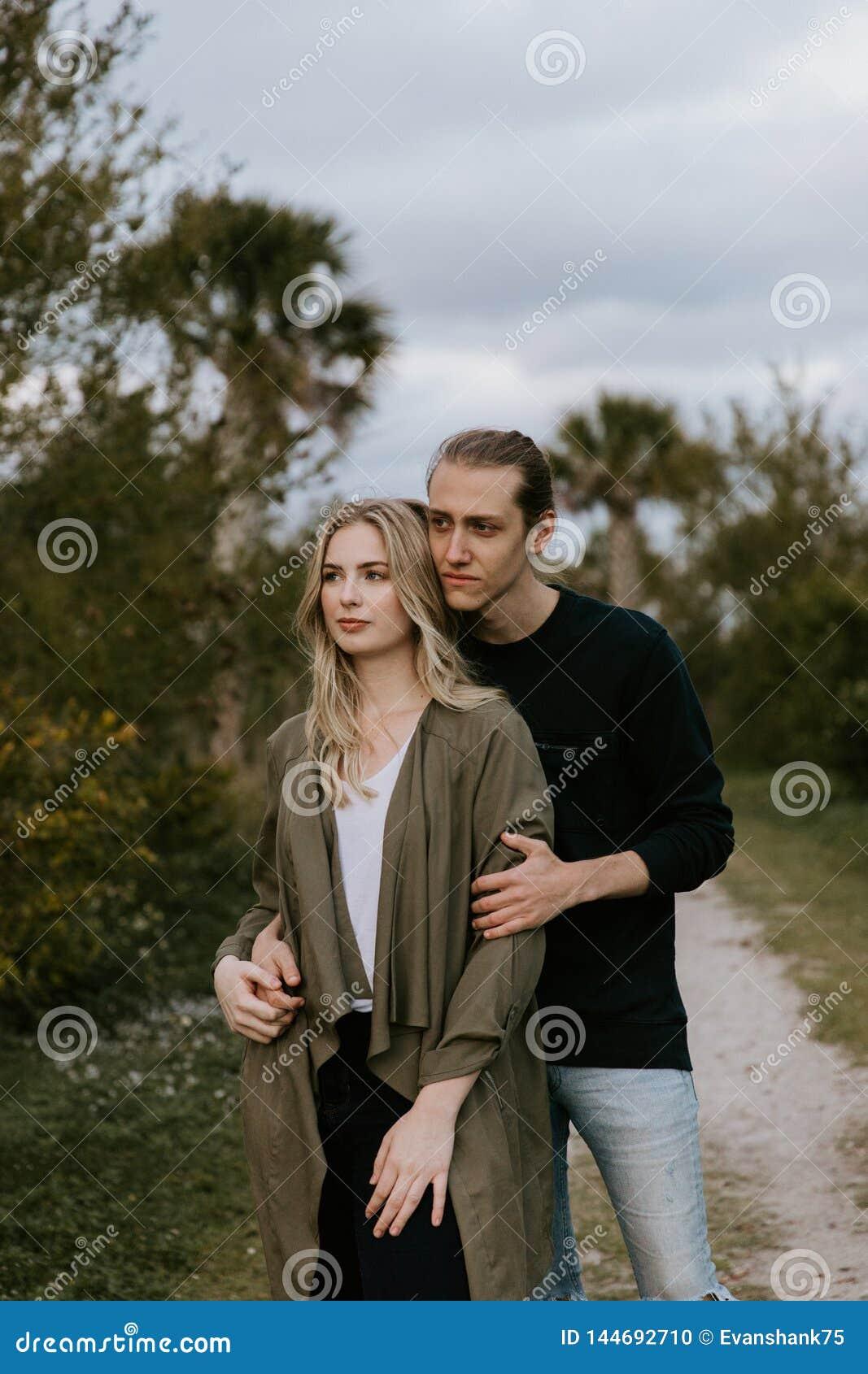 Romantisch en Houdend van Jong Volwassen Paar bij het Park dat Aard bekijkt en de Horizon voor Portretbeelden